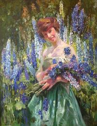Image of a young girl in a green dress surrounded by and holding purple flowers.