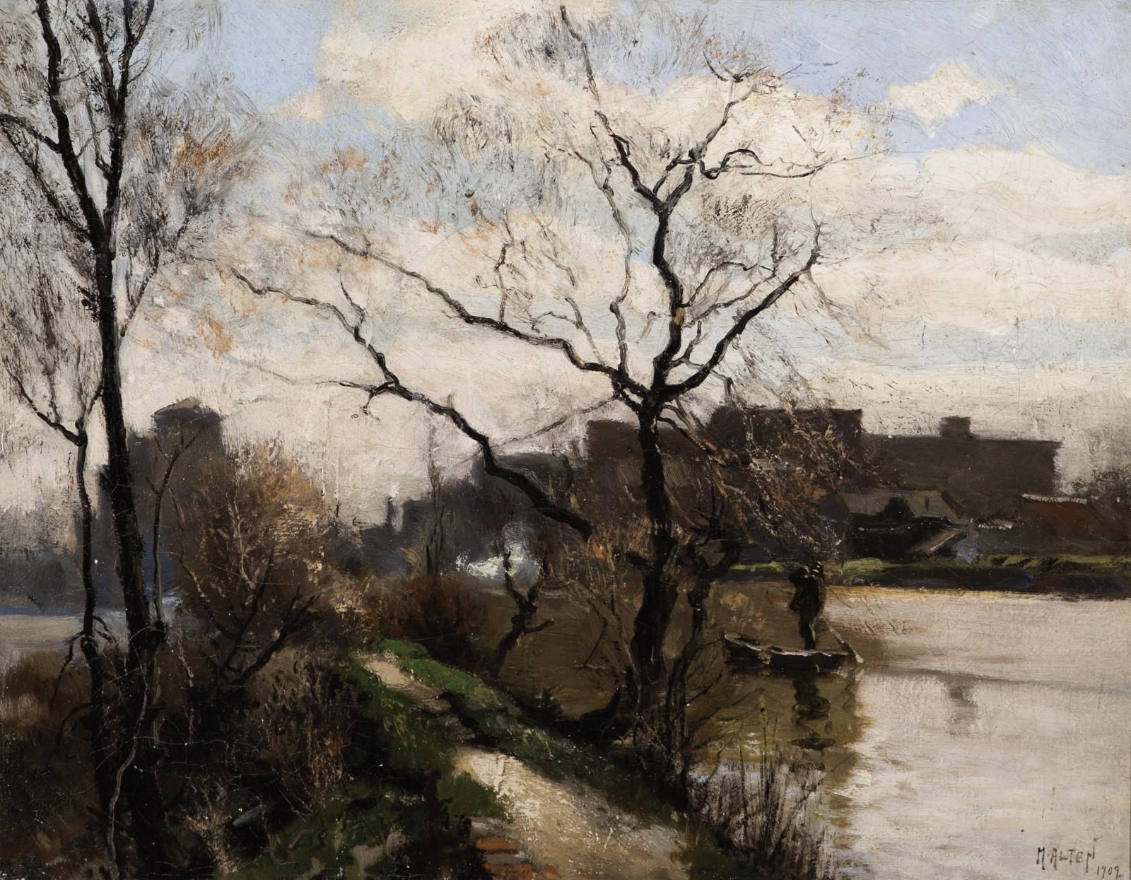 Leafless trees on a small hill near a river with buildings in the background.