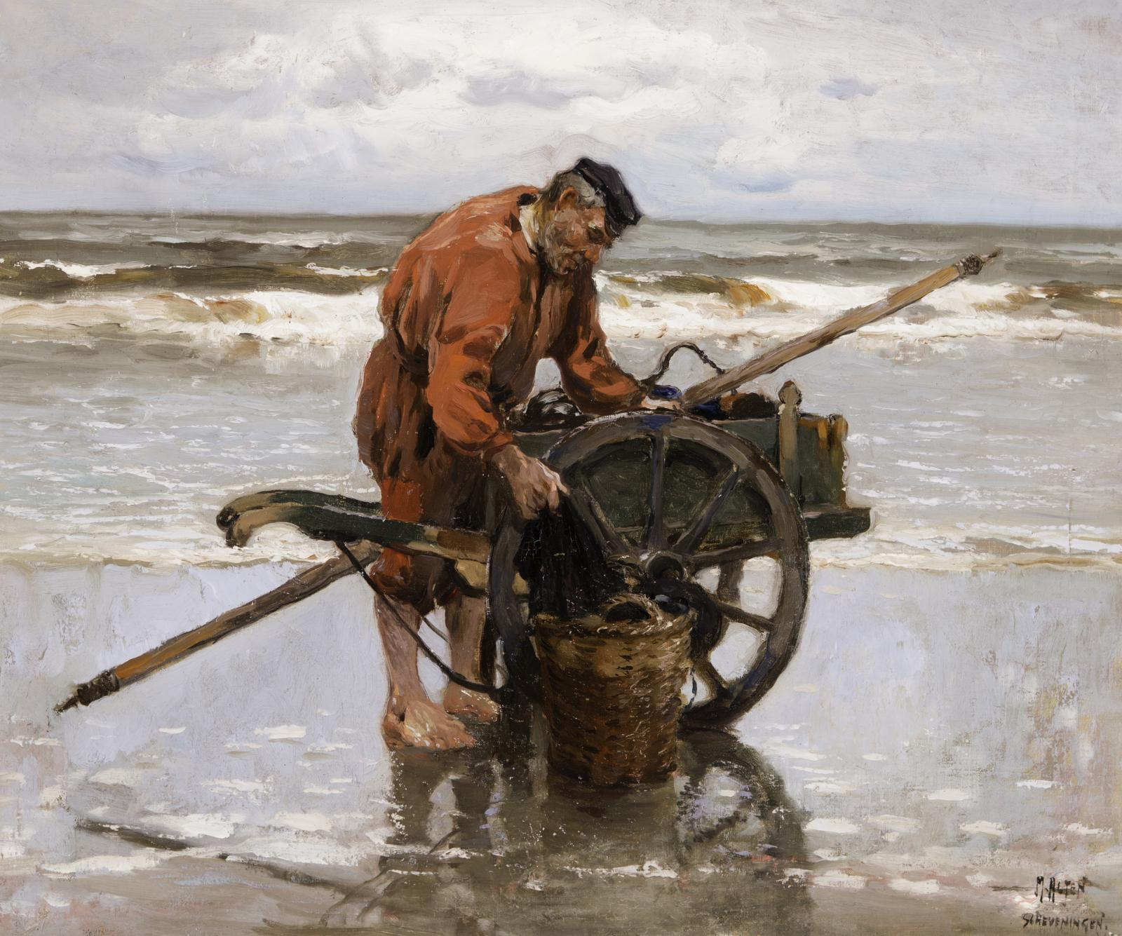 Man in red jacket standing on the beach next to a wooden cart.