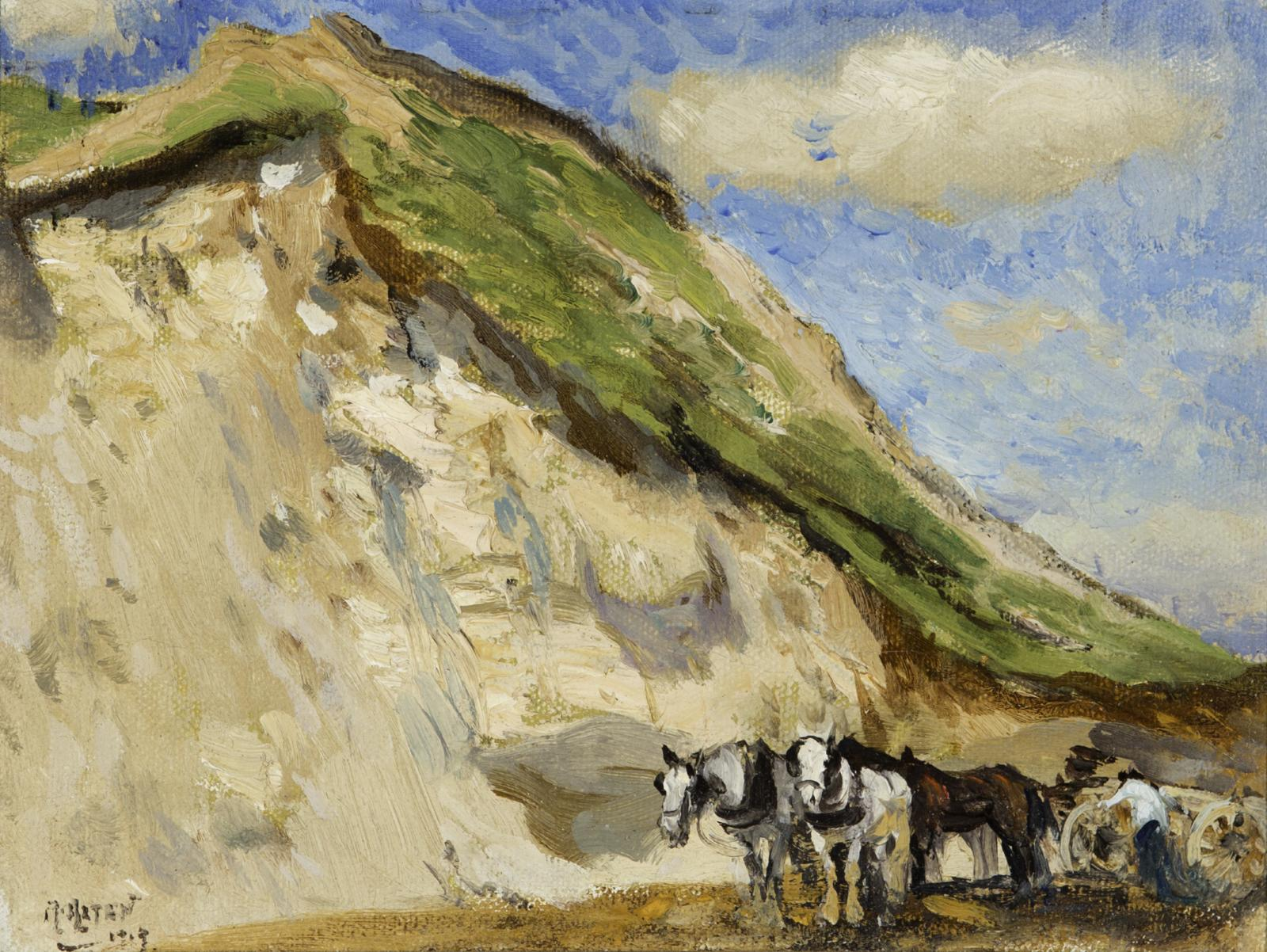 Horses near a large sand dune with green grass on top.