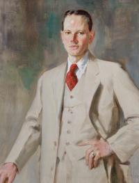 Portrait of man standing with one hand on left hip; wearing light-colored suit with red tie tucked into it.