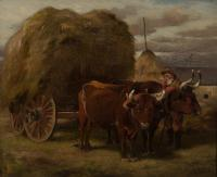 Man with a cart of hay being pulled by two large oxen.