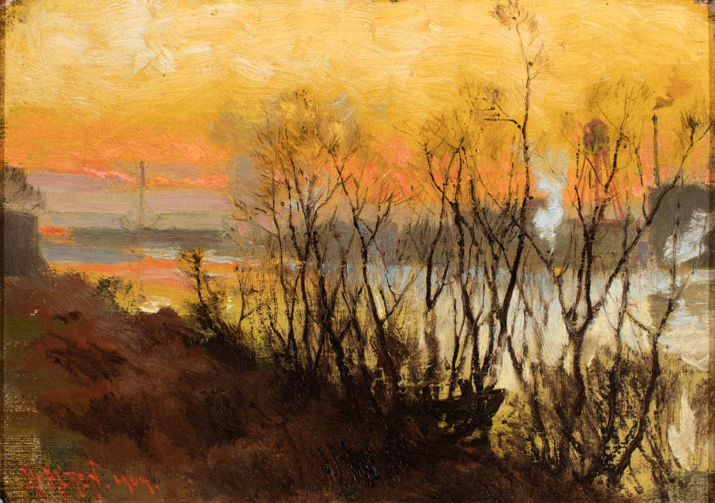 Leafless trees in foreground, river behind and bright sunset in background.