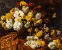 Still life of yellow and white chrysanthemum flowers against a dark background and a fabric covered table.