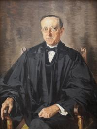 Portrait of a man with glasses seated in a wooden chair wearing black judicial robes.