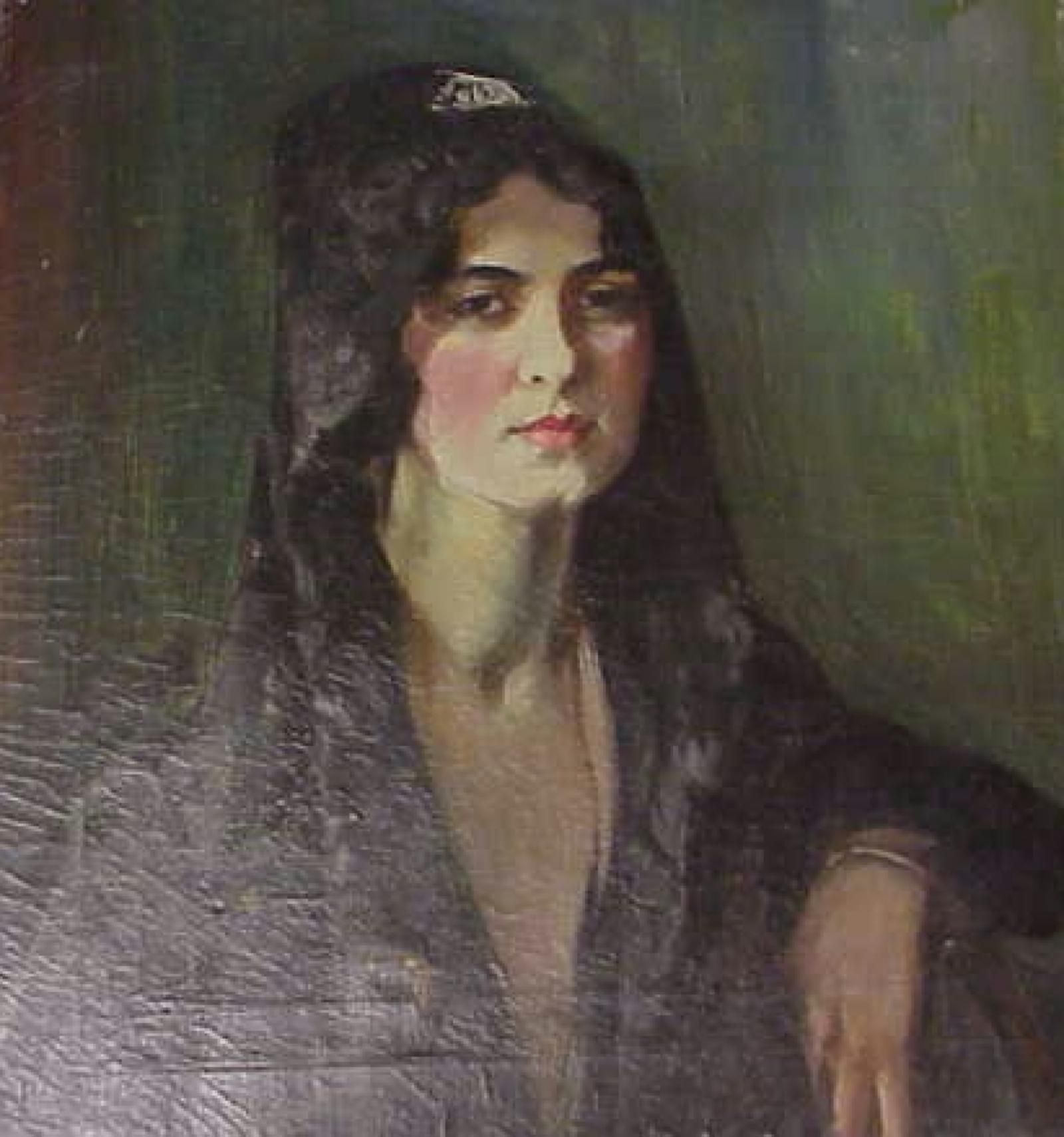 Woman with dark hair and dark veil with a white clip sitting on wooden chair.