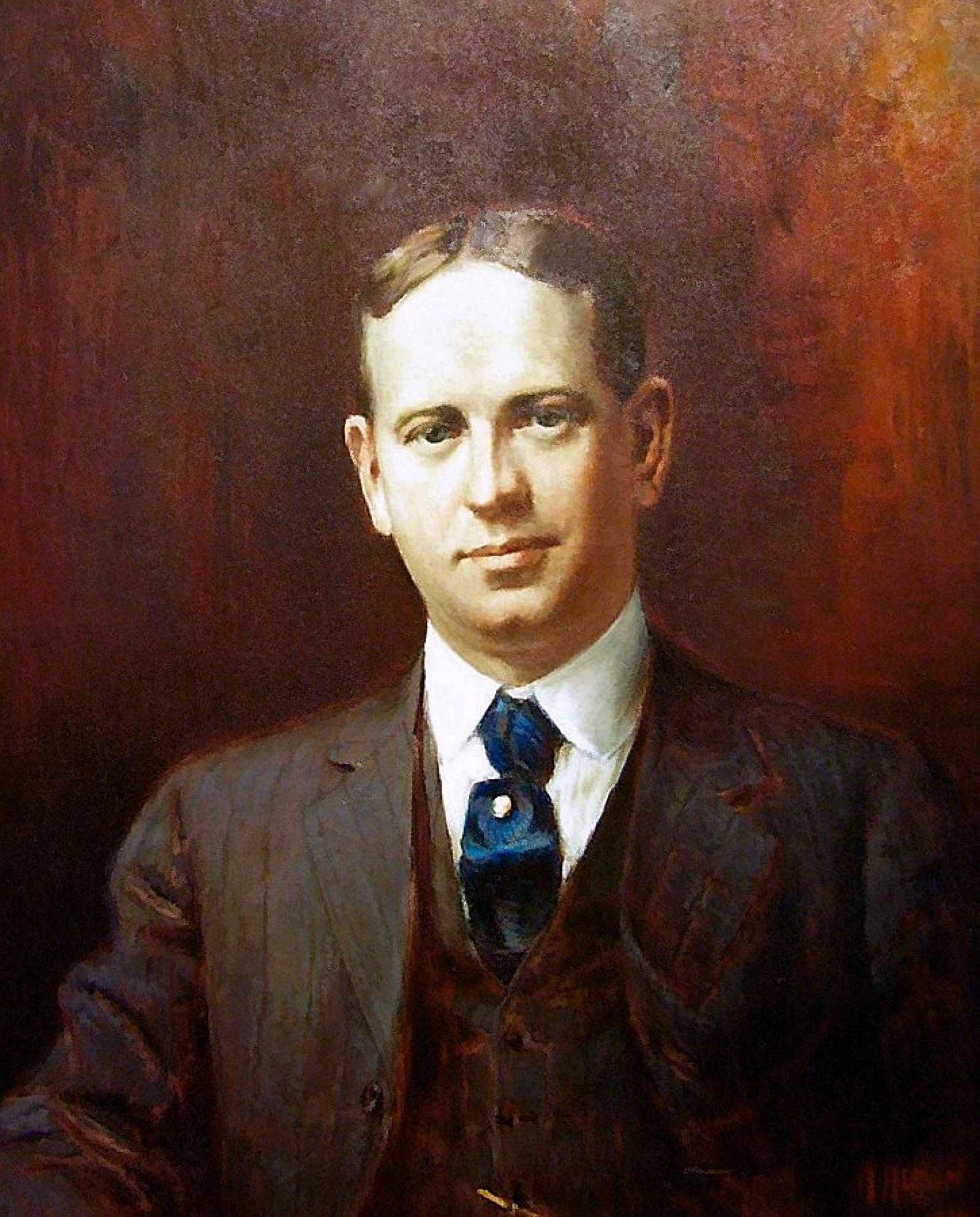 A portrait of a young gentleman in a brown suit and blue tie facing forwards.