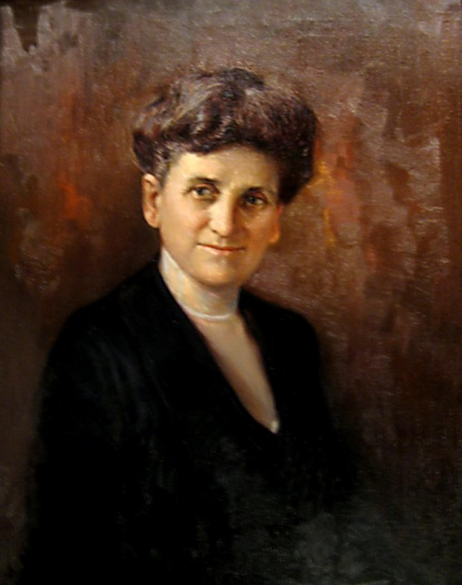 A portrait of an aging woman in a sophisticated black dress wearing a white necklace with her hair piled atop her head, pinned up.