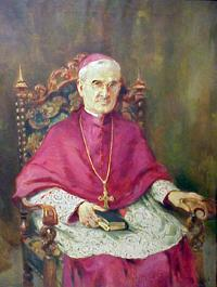 Bishop in red wearing a gold cross sitting in chair with Bible in lap.
