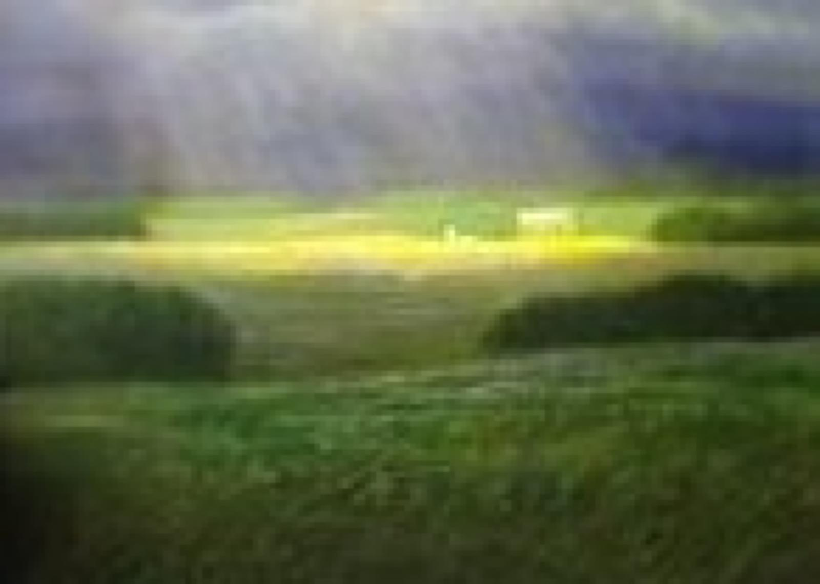 Grass plains with clouded sky showing sunlight through the center.